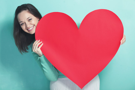 Foto de Woman holding big red heart on blue aqua background - Imagen libre de derechos