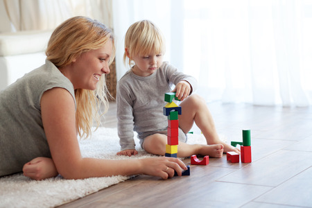 Photo pour Mother with a child playing with wooden blocks at home - image libre de droit