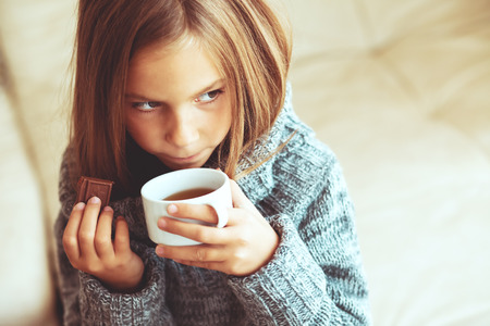 Photo for Child wearing sweater and drinking tea at home - Royalty Free Image