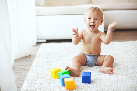 Photo for Toddler playing with toys on a white carpet at home - Royalty Free Image