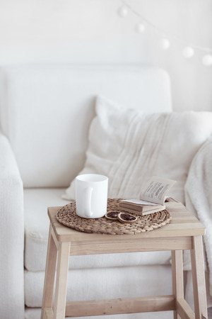 Photo pour Still life interior details, cup of coffee and a book near white cozy chair - image libre de droit
