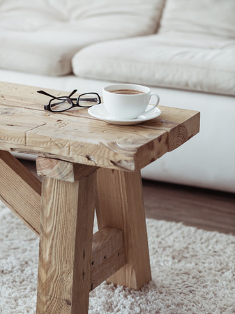 Photo pour Still life details, cup of coffee on rustic bench over white sofa - image libre de droit