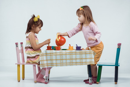 Two 5 years old kids playing with plastic tableware toys