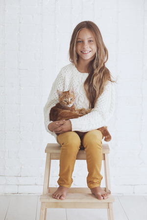 Cute teenage girl 8-9 years old wearing knit trendy winter clothes holding her ginger cat posing over white brick wall