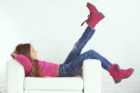 Photo for Cute pre-teen girl wearing fashion winter clothes posing in white interior - Royalty Free Image