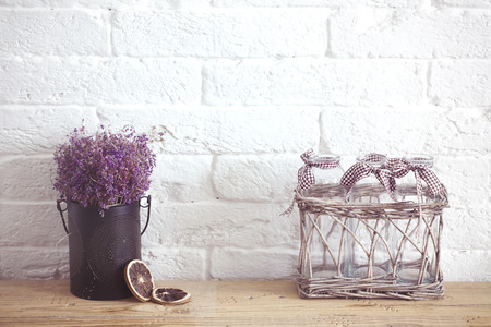 Photo pour Rustic home decor, provence style. Lavender bouquet of dried field flowers and glass spice jars on wooden bench. - image libre de droit