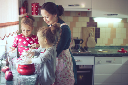 Foto de Mother with her 5 years old kids cooking holiday pie in the kitchen, casual lifestyle photo series in real life interior - Imagen libre de derechos