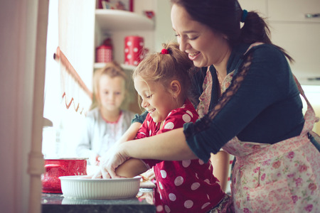 Photo for Mother with her 5 years old kids cooking holiday pie in the kitchen, casual lifestyle photo series in real life interior - Royalty Free Image