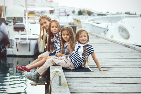 Photo for Group of 4 fashion kids wearing navy clothes in marine style walking in the sea port - Royalty Free Image