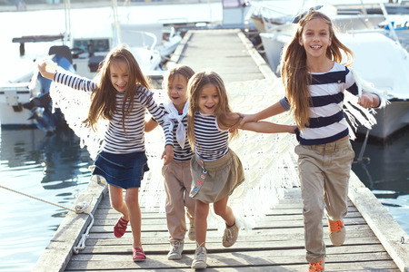 Photo pour Group of 4 fashion kids wearing striped navy clothes in marine style running in the sea port - image libre de droit