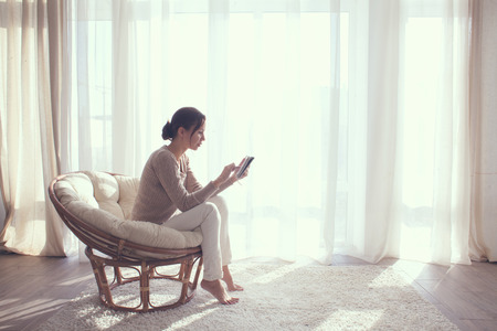 Foto de Young woman at home sitting on modern chair in front of window relaxing in her lliving room using tablet pc - Imagen libre de derechos