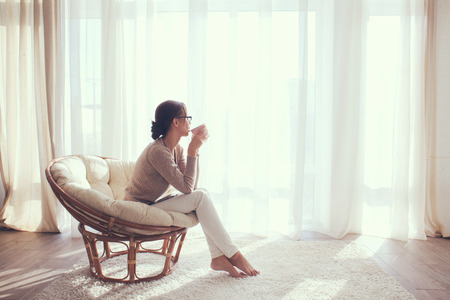 Foto de Young woman at home sitting on modern chair in front of window relaxing in her lliving room and drinking coffee or tea - Imagen libre de derechos
