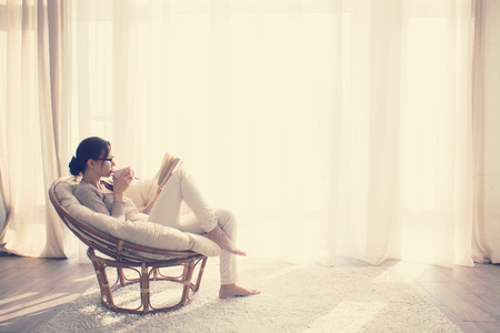 Photo pour Young woman at home sitting on modern chair in front of window relaxing in her lliving room reading book and drinking coffee or tea - image libre de droit