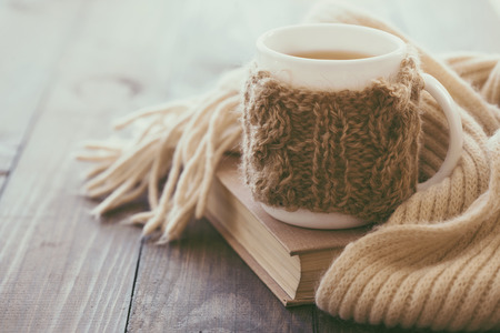 Photo for Cup of hot tea with lemon dressed in knitted warm winter scarf on brown wooden tabletop, soft focus - Royalty Free Image