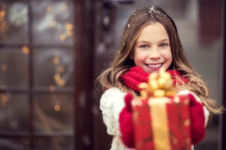 Foto de Child giving a Christmas present near her house door, snowy outside - Imagen libre de derechos