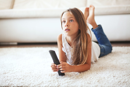 Foto de 8 years old child watching tv laying down on a white carpet at home alone - Imagen libre de derechos