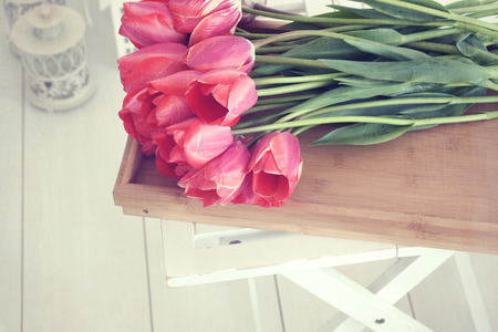Vintage shabby chic photo of bouquet of spring tulips on a wooden tray on white wooden floor
