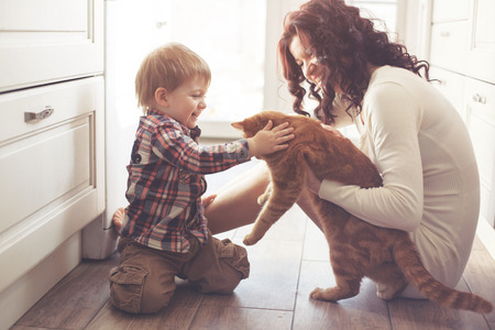Foto für Mother with her baby playing with pet on the floor at the kitchen at home - Lizenzfreies Bild