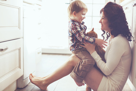 Foto de Mother with her baby playing with pet on the floor at the kitchen at home - Imagen libre de derechos