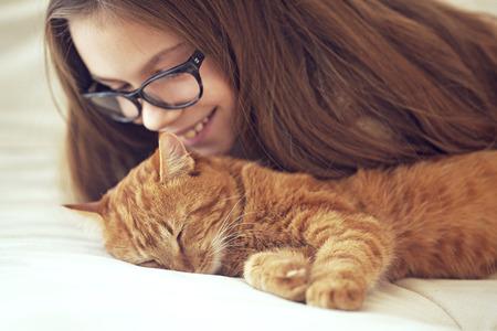 Photo pour Cute ginger cat sleeps near kid girl on the sofa - image libre de droit
