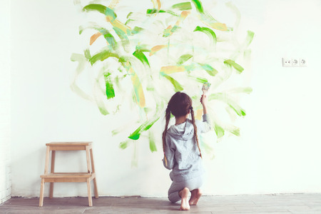 Foto de 8 years old girl painting the wall at home  - Imagen libre de derechos