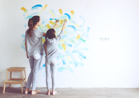 Photo pour 8 years old girl painting the wall at home  - image libre de droit