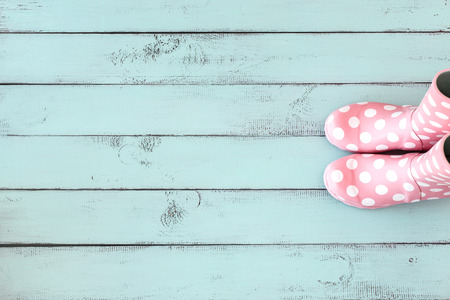 Photo pour Pink polka dot rain boots on mint blue shabby chic wooden background, top view point - image libre de droit