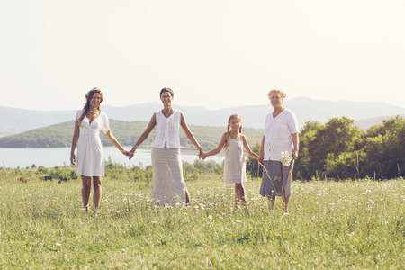 Photo pour Four generations of beautiful women standing together in a camomile field and smiling - image libre de droit