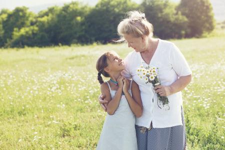 Foto de Great-grandmother and granddaughter standing in flower field in sunlight - Imagen libre de derechos