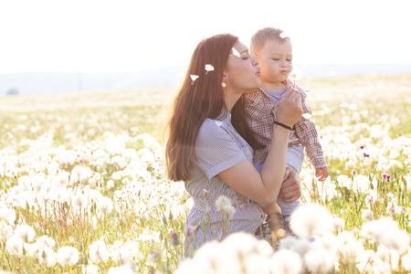 Foto de Mother and her child playing in spring field in soft sunlight - Imagen libre de derechos