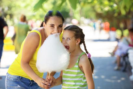 Foto de Child eats cotton candy with mom in city street - Imagen libre de derechos