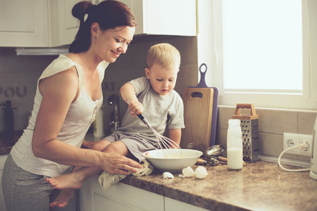 Foto für Mom with her 2 years old child cooking holiday pie in the kitchen to Mothers day, casual lifestyle photo series in real life interior - Lizenzfreies Bild