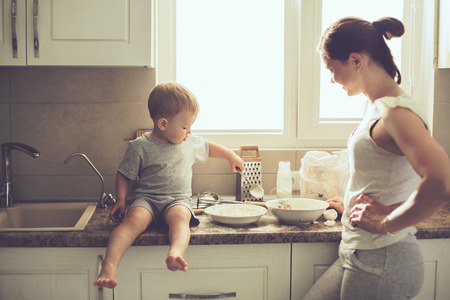 Photo for Mom with her 2 years old child cooking holiday pie in the kitchen to Mothers day, casual lifestyle photo series in real life interior - Royalty Free Image