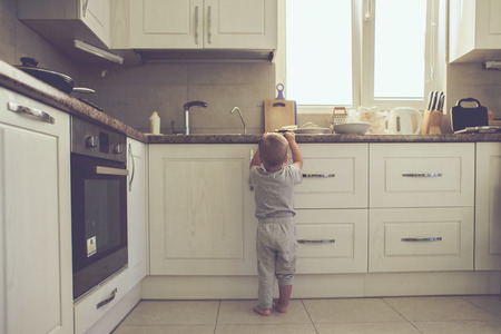 Foto de 2 years old child standing on the floor alone in the kitchen, casual lifestyle photo series in real life interior - Imagen libre de derechos