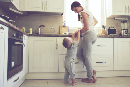 Foto de Mom with her 2 years old child cooking holiday pie in the kitchen to Mothers day, casual lifestyle photo series in real life interior - Imagen libre de derechos
