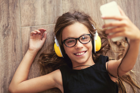 Photo pour 9 years old child is lying down on the floor, listening to music and taking selfie, top view point - image libre de droit
