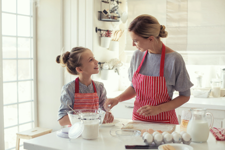 Foto de Mom with her 9 years old daughter are cooking in the kitchen to Mothers day, lifestyle photo series in bright home interior - Imagen libre de derechos