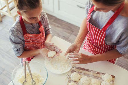 Photo for Mom with her 9 years old daughter are cooking in the kitchen to Mothers day, lifestyle photo series in bright home interior - Royalty Free Image