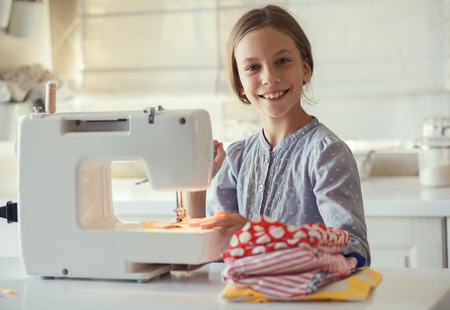 Foto de 9 years old child studying work with sewing machine - Imagen libre de derechos