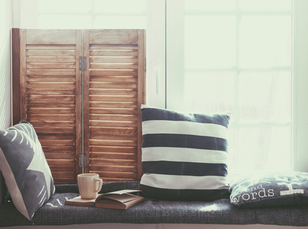 Photo for Warm and cozy window seat with cushions and a opened book, light through vintage shutters, rustic style home decor. - Royalty Free Image
