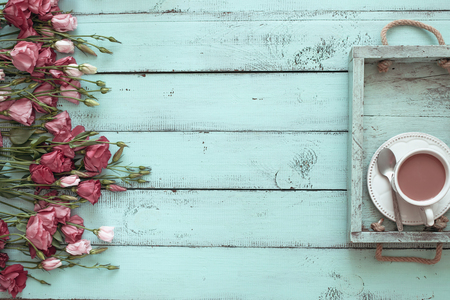Photo for Vintage wooden tray with porcelain teacup and pink flowers on shabby chic mint background, top view point - Royalty Free Image