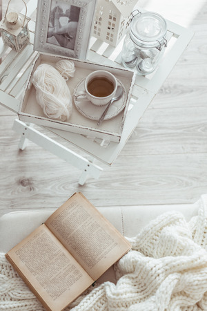 Photo pour Still life details, cup of tea on retro vintage wooden tray on a coffee table in living room, top view point. Lazy winter weekend with a book on the sofa. - image libre de droit
