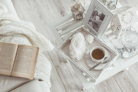 Photo for Still life details, cup of tea on retro vintage wooden tray on a coffee table in living room, top view point. Lazy winter weekend with a book on the sofa. - Royalty Free Image