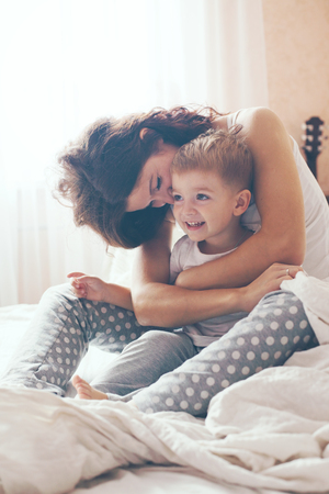 Foto de Young mother with her 2 years old little son dressed in pajamas are relaxing and playing in the bed at the weekend together, lazy morning, warm and cozy scene. Pastel colors, selective focus. - Imagen libre de derechos