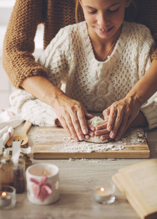 Photo pour Mom with her 9 years old daughter are cooking holiday pie in the kitchen, lifestyle photo series, hands closeup. - image libre de droit