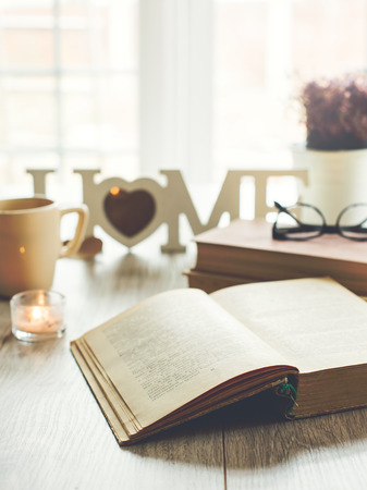 Photo for Sweet home. Opened book with glasses, candle and cup of tea on background, selective focus. Text in a book is not recognizible. - Royalty Free Image