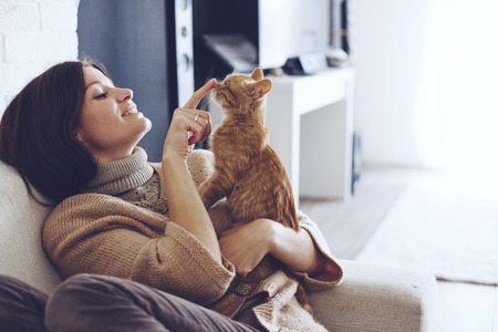 Foto de Young woman wearing warm sweater is resting with a cat on the armchair at home one autumn day - Imagen libre de derechos