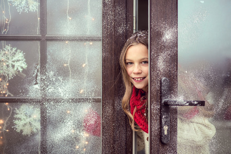 Photo for Child girl opens dor and welcome guests, snow weather, house is decorated for Christmas - Royalty Free Image