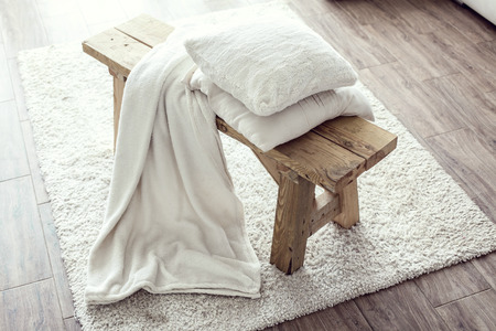 Photo pour Still life details, stack of white cushions and blanket on rustic bench on white carpet - image libre de droit