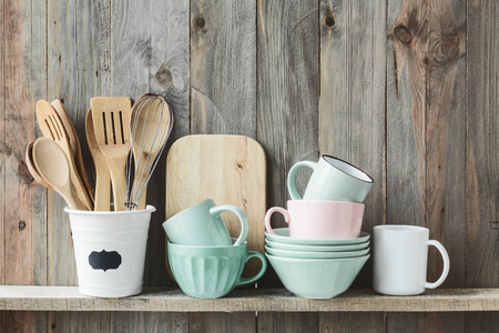 Foto de Kitchen cooking utensils in ceramic storage pot on a shelf on a rustic wooden wall - Imagen libre de derechos